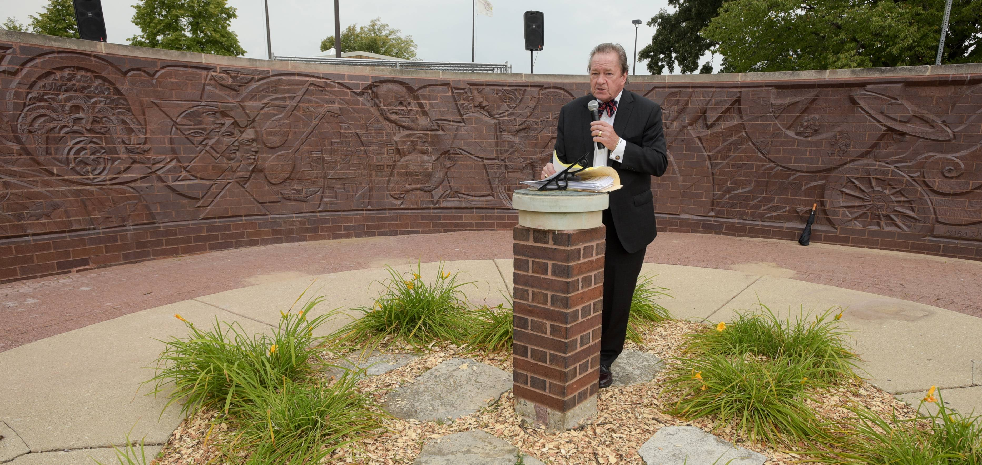 "Brand Bobosky, Chairman of Century Walk Corp. presides over the rededication Wednesday afternoon of the repaired sculpture ""Man's Search for Knowledge Through the Ages"" outside Nichols Library in downtown Naperville. The art was restored after it was damaged last summer in a crash."