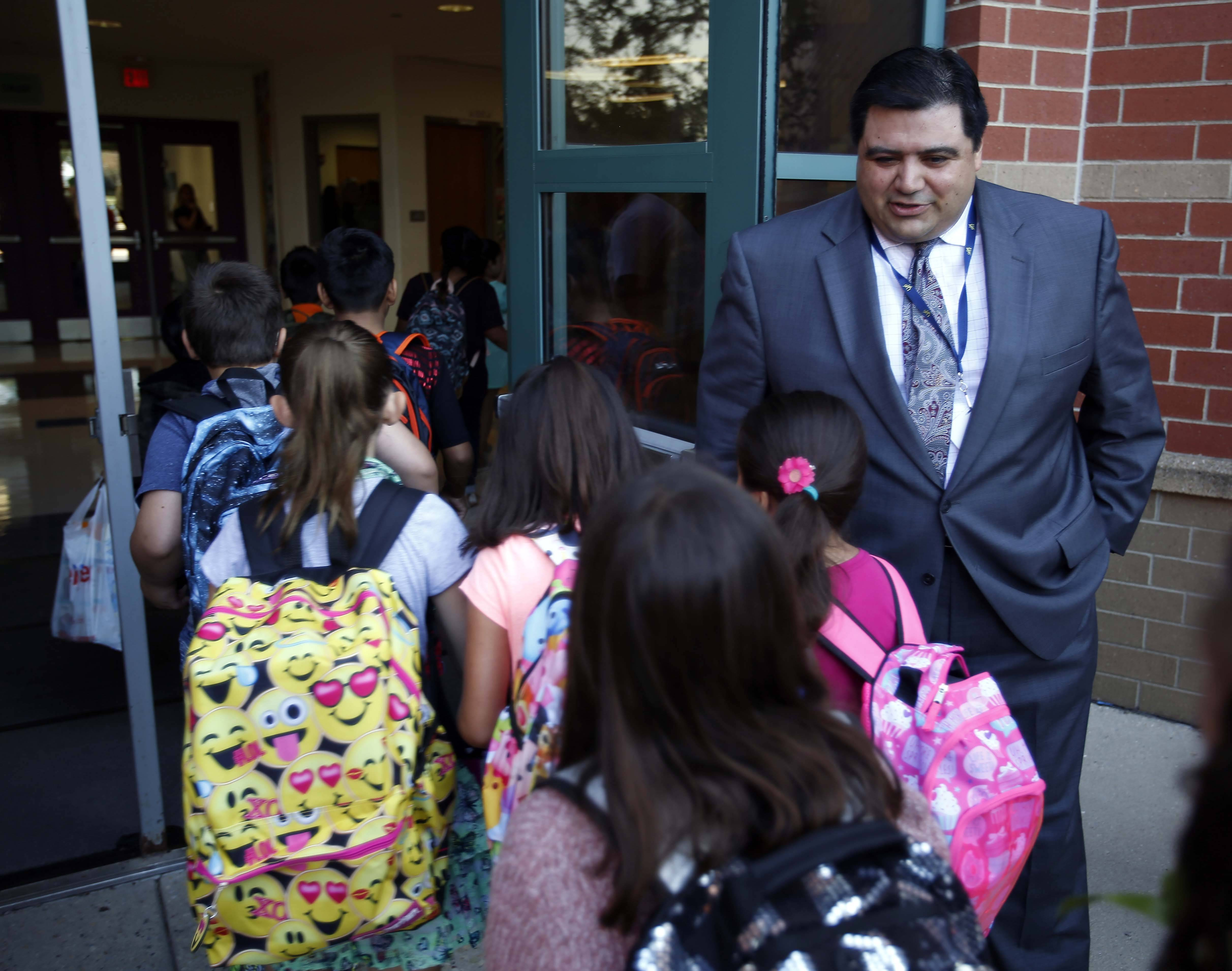 New Otter Creek Elementary School Principal David Aleman greets students Wednesday on their first day of classes. Aleman was a classroom teacher at Elgin Area School District U-46's Ellis Middle School, and Spring Trail and Channing Memorial elementary schools.