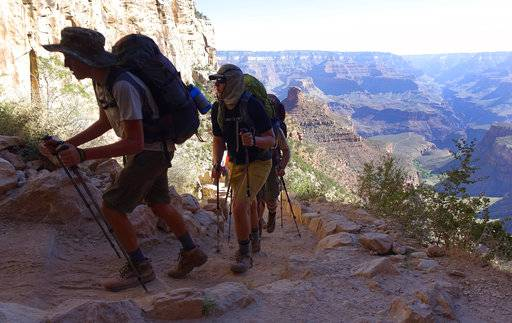 FILE - In this July 27, 2015, file photo, a long line of hikers head out of the Grand Canyon along the Bright Angel Trail at Grand Canyon National Park, Ariz. The U.S. federal government announced Wednesday, Aug. 16, 2017, it will eliminate a policy it put in place to allow national parks like the Grand Canyon to ban the sale of bottled water in an effort to curb litter. (AP Photo/Ross D. Franklin, File)
