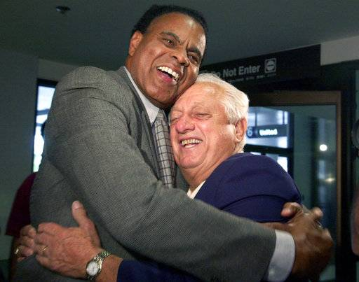 FILE - In this Sept. 28, 2000, file photo, Tommy Hawkins, left, Los Angeles Dodgers vice president of external affairs, left, greets Tommy Lasorda, former Dodgers manager and manager of the American gold medal Olympics baseball team, on the team's arrival at Los Angeles International Airport from Australia. Hawkins, the first black athlete to earn All-America honors in basketball at Notre Dame and who played for the Los Angeles Lakers during a 10-year NBA career, has died. He was 80. (AP Photo/Kim D. Johnson, File)