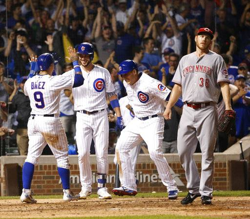 Chicago Cubs' Javier Baez (9) celebrates with Kris Bryant and Anthony Rizzo after Baez scored the game winning-run on a wild pitch from Cincinnati Reds' Blake Wood, right, during the ninth inning of a baseball game Wednesday, Aug. 16, 2017, in Chicago. The Cubs won 7-6. (AP Photo/Charles Rex Arbogast)