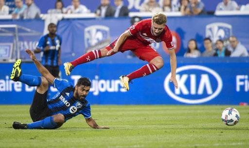 Chicago Fire midfielder Djordje Mihailovic trips over Montreal Impact defender Victor Cabrera during the first half of an MLS soccer match Wednesday, Aug. 16, 2017, in Montreal. (Paul Chiasson/The Canadian Press via AP)