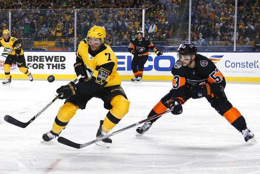 FILE - In this Feb. 25, 2017, file photo, Pittsburgh Penguins' Matt Cullen (7) and Philadelphia Flyers' Shayne Gostisbehere (53) vie for the puck during the first period of an NHL hockey game at Heinz Field in Pittsburgh. The Minnesota Wild and Cullen have agreed to a one-year, $1 million contract, bringing him back to his home state for a 21st season in the NHL. The Wild announced the deal, which includes $700,000 in potential performance bonuses, on Wednesday, Aug. 16, 2017. (AP Photo/Gene J. Puskar, File)