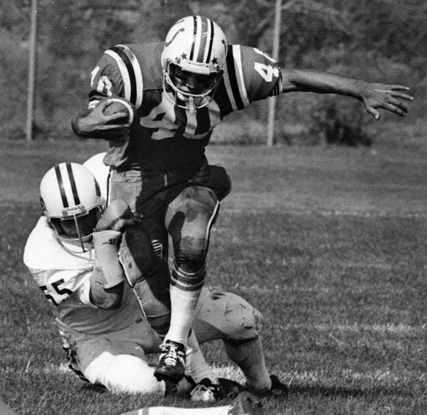 A Barrington running back drags and Elk Grove defender during their game in 1977.