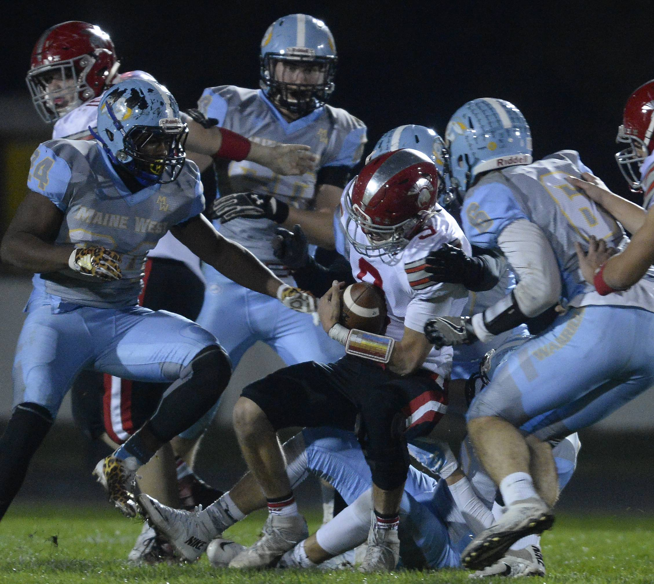 Maine West's defense brings down Deerfield's quarterback Jonah Silverglade in the first half of boys football at Maine West on Friday.