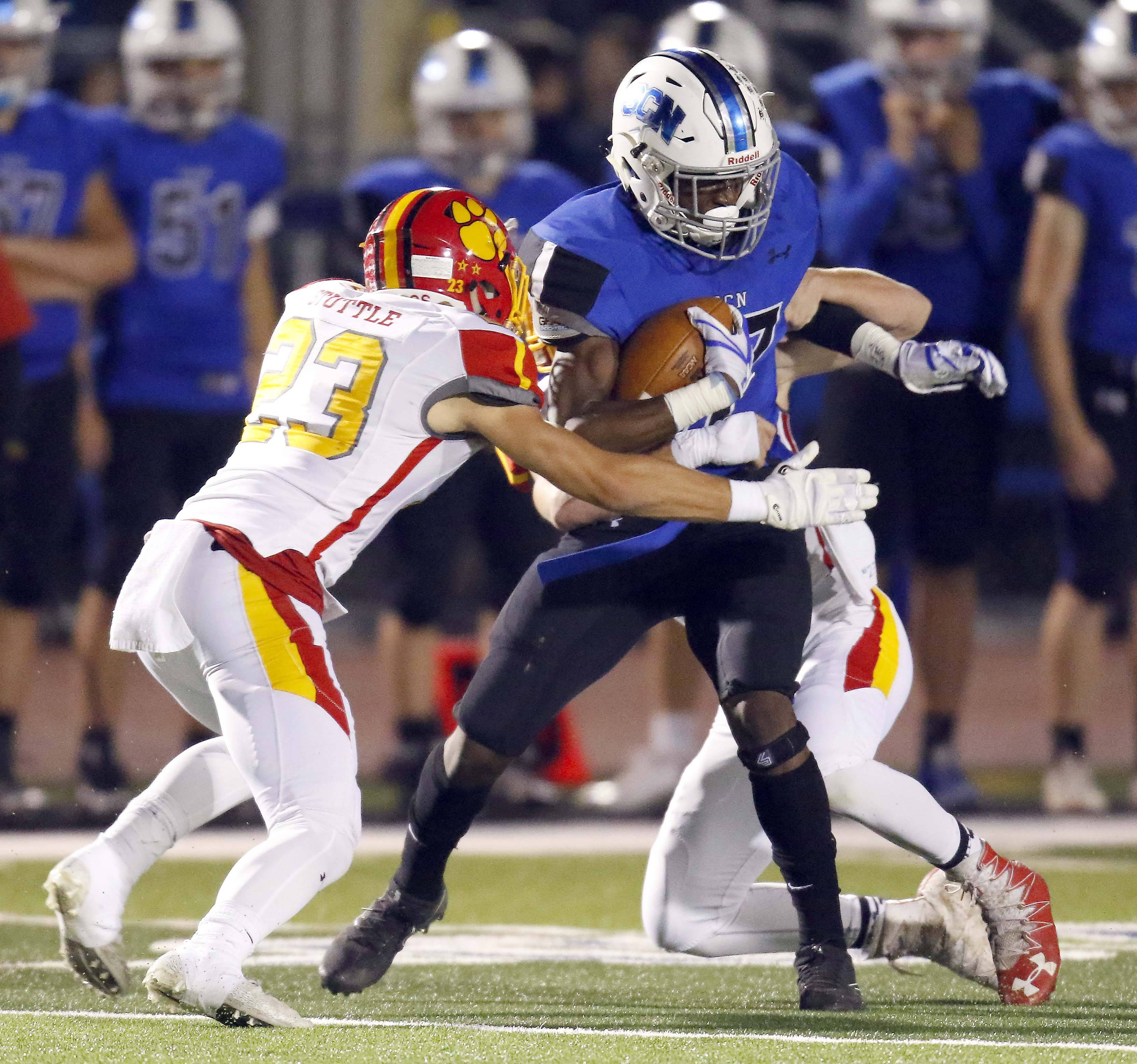 St. Charles North's Tyler Nubin (27) is wrapped up by Batavia's Tom Stuttle (23) during Batavia at St. Charles North football Friday, Oct. 20 2017.