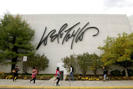 FILE - In this Wednesday, Oct. 25, 2017, file photo, people walk on a sidewalk along the entrance to Lord & Taylor department store at Garden State Plaza in Paramus, N.J. Walmart announced Monday, Nov. 13, 2017, that it will devote a section on its website to upscale Lord & Taylor, the latest strategic partnership as retailers make alliances.