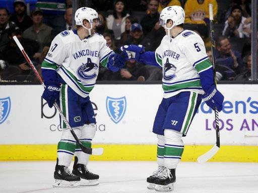 Vancouver Canucks left wing Sven Baertschi, left, celebrates hisp goal with defenseman Derrick Pouliot during the third period of an NHL hockey game against the Los Angeles Kings in Los Angeles, Tuesday, Nov. 14, 2017. The Canucks won 3-2.