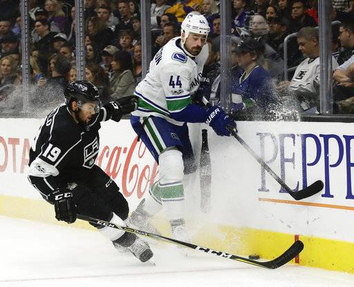 Los Angeles Kings center Alex Iafallo, left, and Vancouver Canucks defenseman Erik Gudbranson race for the puck during the second period of an NHL hockey game in Los Angeles, Tuesday, Nov. 14, 2017.
