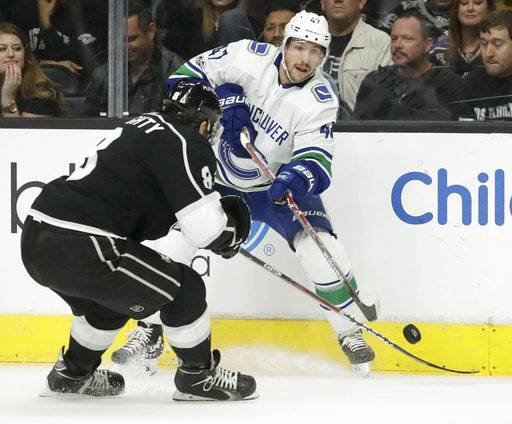 Vancouver Canucks left wing Sven Baertschi, right, passes the puck past Los Angeles Kings defenseman Drew Doughty during the first period of an NHL hockey game in Los Angeles, Tuesday, Nov. 14, 2017.