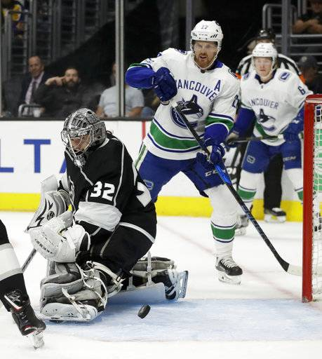 Los Angeles Kings goalie Jonathan Quick, left, blocks a shot as Vancouver Canucks left wing Daniel Sedin watches during the first period of an NHL hockey game in Los Angeles, Tuesday, Nov. 14, 2017.