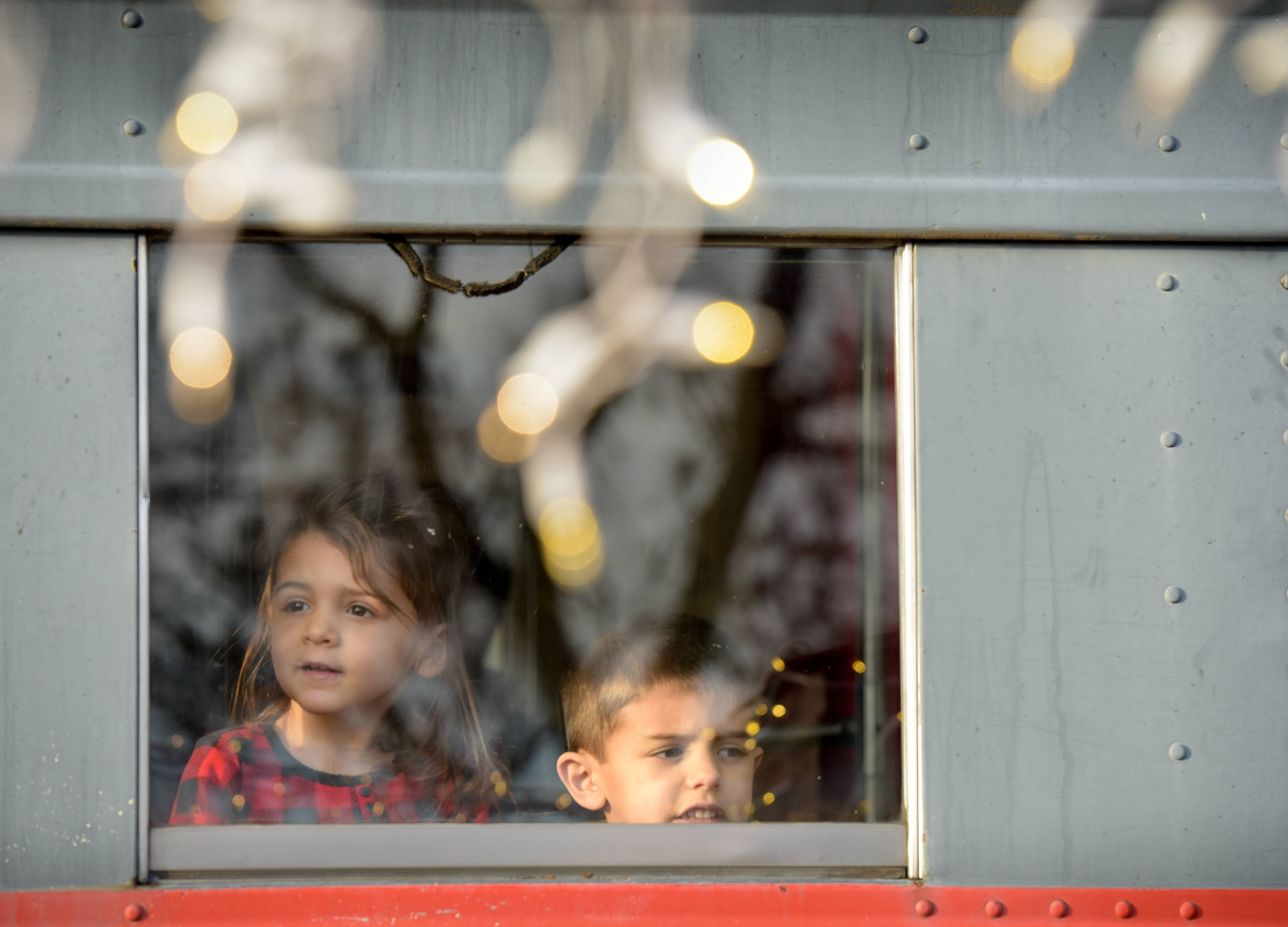 "Arianna Peri, 2 and her brother Vincenzo, 3 of Mount Prospect look out the window of The Polar Express before departing Blackhawk Station in the Jon Duerr Forest Preserve on her way to the ""North Pole"" to see Santa on November 19, 2017."