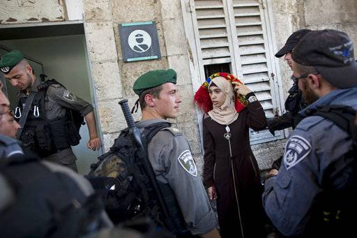 FILE - In this Wednesday, July 19, 2017 file photo Israeli border police officers stop a Palestinian woman for a security check as Palestinians gather for prayer at the Lion's Gate, following an appeal from clerics for Muslims to pray in the streets instead of the Al-Aqsa Mosque compound, in Jerusalem's Old City. U.S. officials say President Donald Trump will recognize Jerusalem as Israel's capital Wednesday, Dec. 6, and instruct the State Department to begin the multi-year process of moving the American embassy from Tel Aviv to the holy city. (AP Photo/Oded Balilty, File)The Associated Press