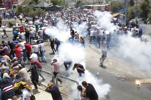 FILE - In this Friday, July 21, 2017, file photo, Palestinians run away from tear gas thrown by Israeli police officers outside Jerusalem's Old City. U.S. officials say President Donald Trump will recognize Jerusalem as Israel's capital Wednesday, Dec. 6, and instruct the State Department to begin the multi-year process of moving the American embassy from Tel Aviv to the holy city. His decision could have deep repercussions across the region. (AP Photo/Mahmoud Illean, File)The Associated Press