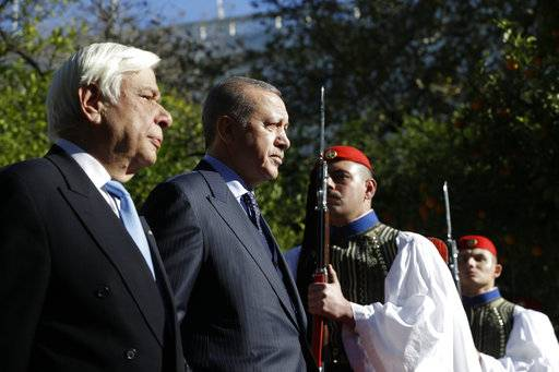 Greece's President Prokopis Pavlopoulos, left and Turkey's President Recep Tayyip Erdogan, centre, review the Presidential Guard during the welcome ceremony in Athens, Thursday, Dec. 7, 2017. Erdogan arrived in Athens Thursday for a two-day official visit, the first official visit by a Turkish president in decades, with Greece hoping the trip will help improve often frosty ties with its neighbour.