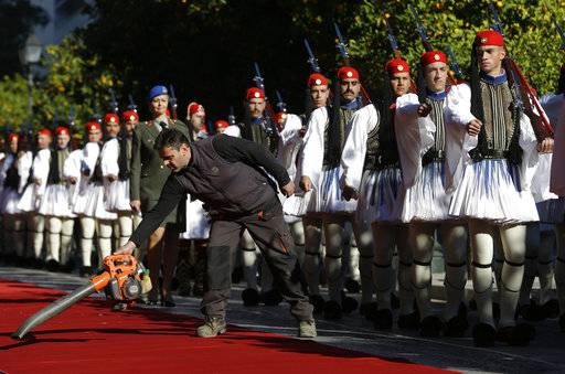 A worker cleans the red carpet as Greek Presidential Guards march to their positions for the official welcome ceremony for Turkey's President Recep Tayyip Erdogan, in Athens, Thursday, Dec. 7, 2017. Erdogan is in Greece on a two-day official visit.